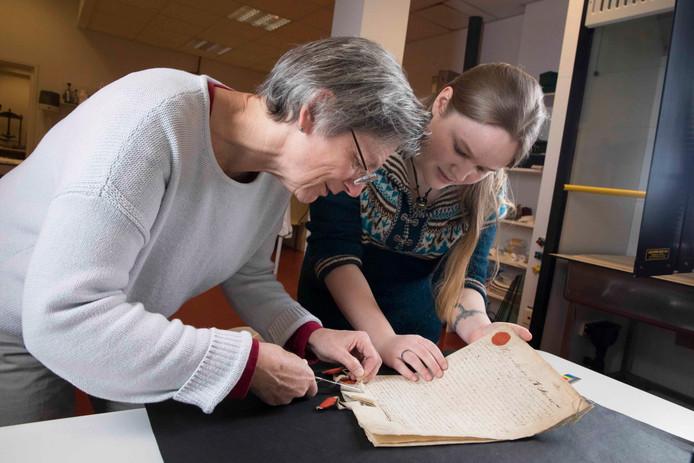 Willemien Janden (r) en Lisa Winters openen een van de testamenten.