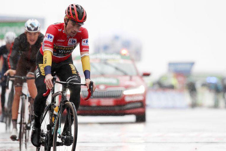 Primoz Roglic komt doorweekt over de streep in de Vuelta. Hij verloor tijd door problemen met zijn regenvestje. Beeld Photo News
