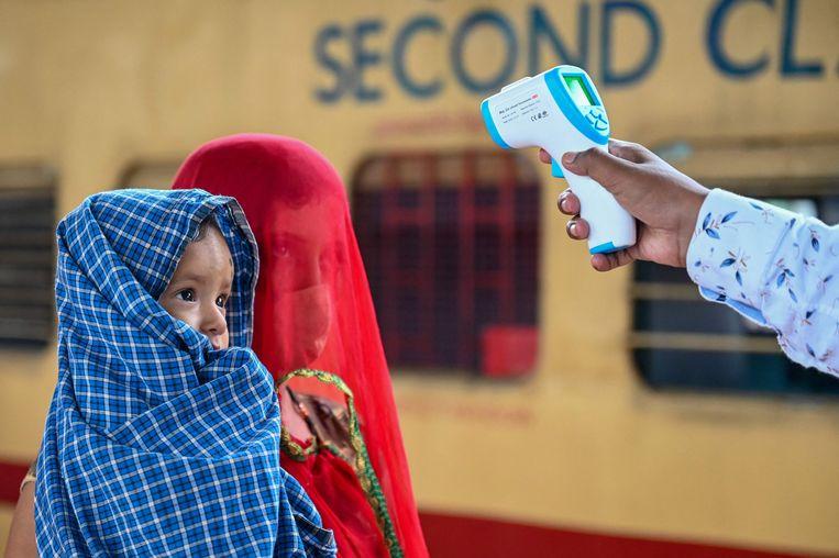 De temperatuur van een moeder en een dochter in Mumbai wordt gecheckt. Beeld AFP