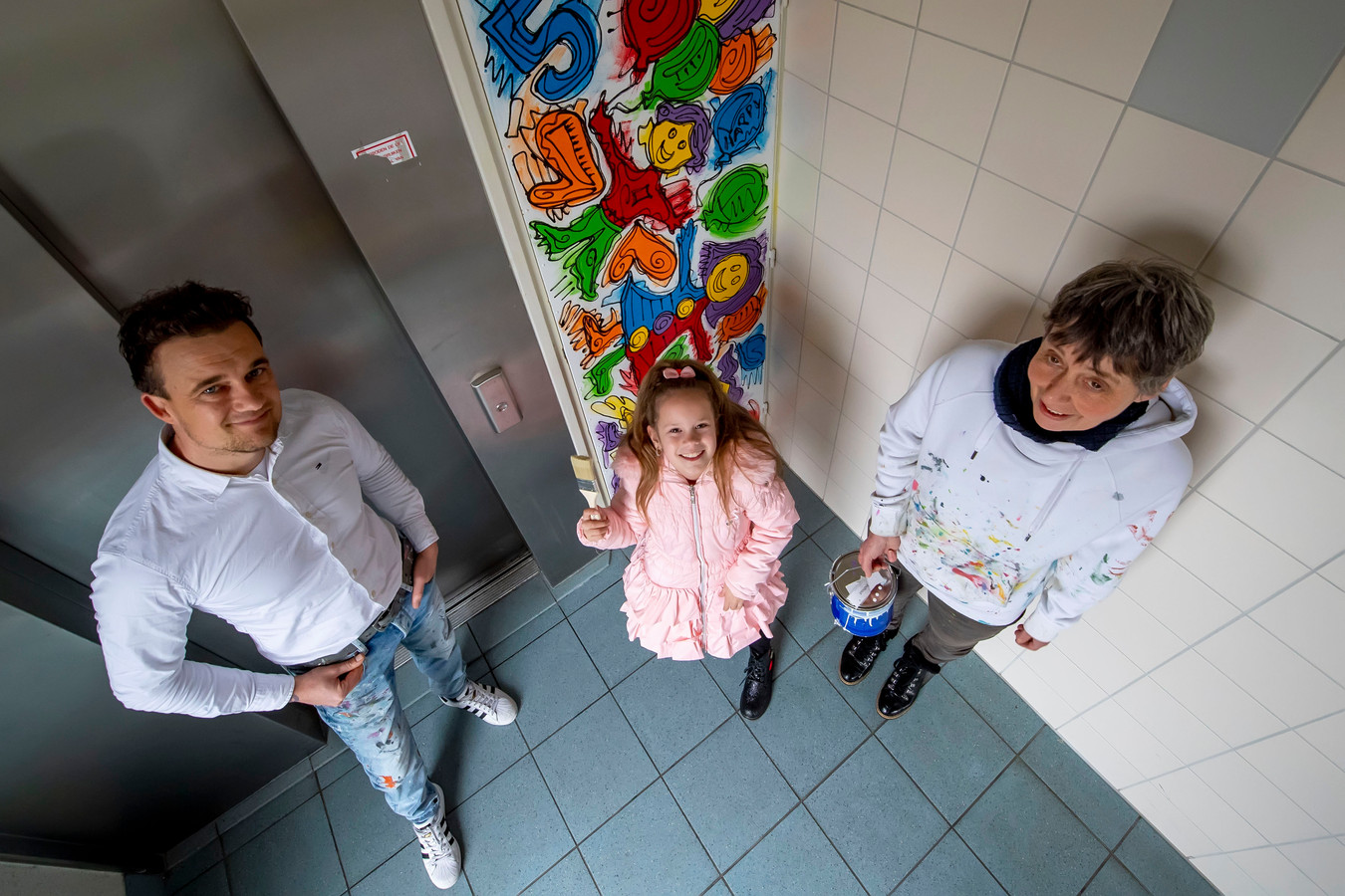v.l.n.r. : kunstenaar Iwaz, Macey (buurtbewoner) & initiatiefneemster Anny Luijsterburg bij één van de schilderingen in de Heiningen flats.