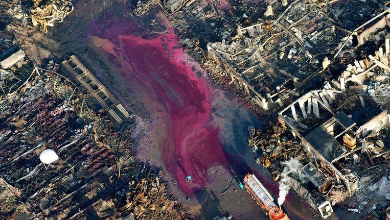 Bij het het chemiebedrijf Chemie-Pack in Moerdijk wordt begin januari het door chemicalien gekleurde bluswater weggezogen. Het bedrijf werd door een grote brand volledig verwoest. © ANP Beeld