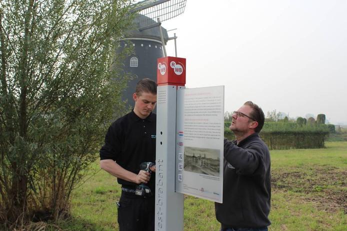 Bij het plaatsen van de Van Goghzuil helpt vormgever Peter van Kemenade (rechts) zelf mee. Foto Herbert Kats