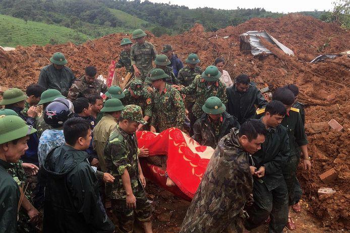 Reddingswerkers halen een lichaam van onder de modder en het steenpuin.