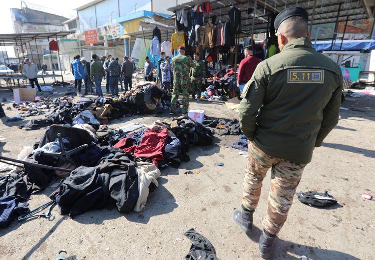 Kledingstukken bedekken de plek des onheils. De aanslagen gebeurden op een drukke kledingmarkt. Beeld EPA