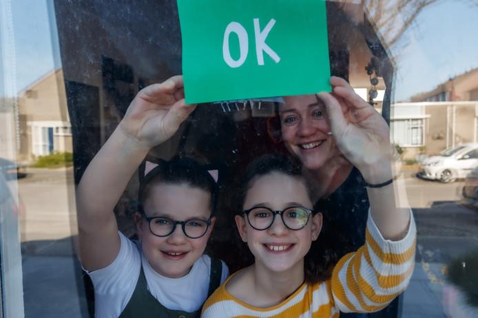 Rachel de Korte en haar twee dochters Fleur en Ella zijn een rode en groene kaartenactie begonnen vanwege de coronacrisis. Groene kaart achter het raam: alles is in orde. Rode kaart achter het raam: ik kan hulp gebruiken.