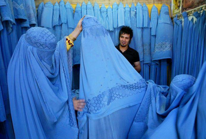 Une femme afghane regarde la marchandise dans une boutique de burqa à Herat, dans l'ouest de l'Afghanistan, le 2 juillet 2009.