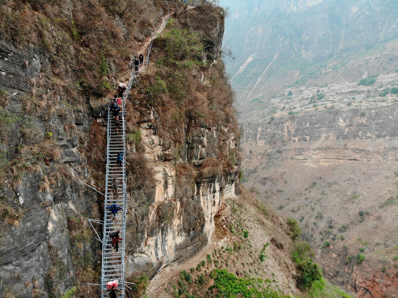 Het Chinese bergdorpje Atulie'er, gelegen op een rotswand, is alleen per ladder bereikbaar. In 2017 werd de rafelige touwladder vervangen door een stalen exemplaar.   Beeld Hu Longchuan/AP