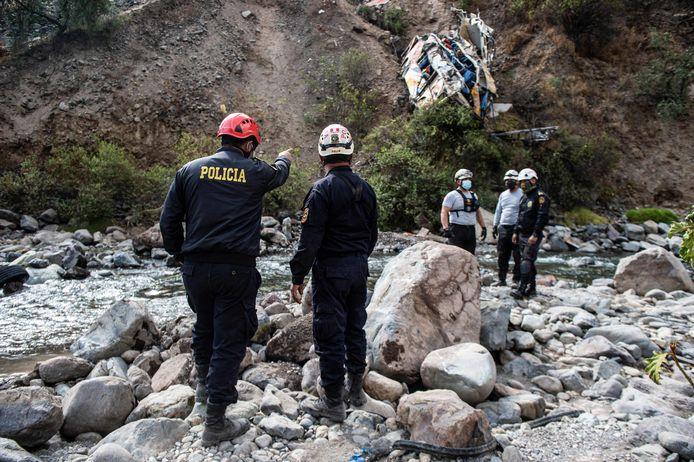 Reddingswerkers en politieagenten bij de plek waar de bus naar beneden stortte.