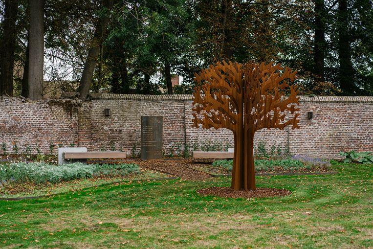 Een gedenkplaat in de rozentuin van het Speelhof in Sint-Truiden herinnert aan de overledenen van Covid-19. Beeld Wouter Van Vooren