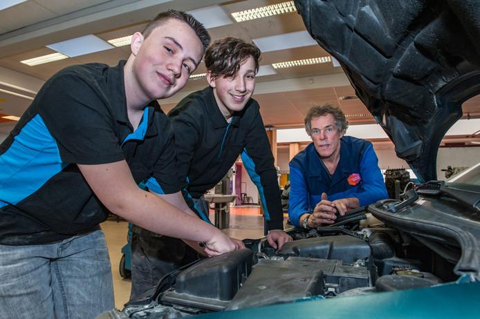 Jordy (15) en Mohammed (14) sleutelen onder begeleiding van docent Henk Oudshoorn aan een auto tijdens de techniekles op de Goudse Waarden.
