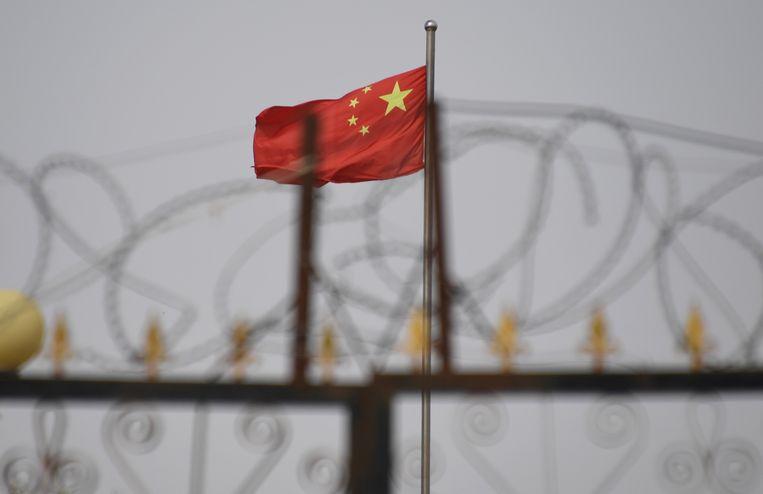Op deze foto uit 2019 wappert de Chinese vlag achter de hekken van een kamp in Yangisar, in de westelijke regio Xinjiang. Volgens mensenrechtenorganisaties worden Oeigoeren daar vastgehouden.  Beeld AFP