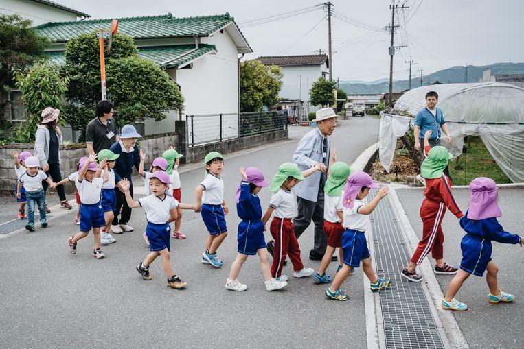 Piepjong en stokoud samen op weg naar het station van Ukiha om de luxetrein 'Zeven sterren in Kyushu' te bekijken. Beeld Jun Michael Park/laif