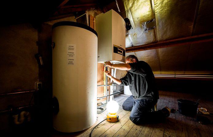 Een erkende installateur is bezig met het installeren van een warmtepomp bij een verwarmingsketel, als onderdeel van een project om een jaren 60-woning energiezuinig te maken.