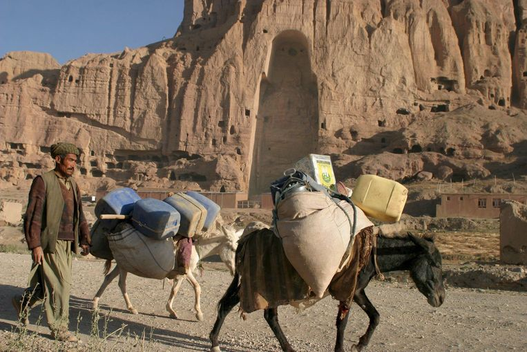 Een man loopt met zijn ezels langs de nis in Bamyan waar de 1600 jaar oude boeddhabeelden stonden. De taliban vernietigden de beelden in 2001.  Beeld EPA