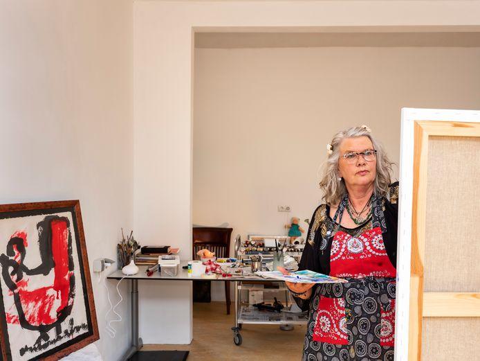 Emeke in haar atelier met links een schilderij van Anton Heyboer.