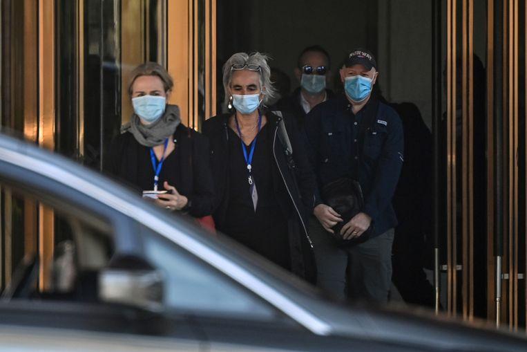 Marion Koopmans, Peter Daszak en andere onderzoekers van het WHO-team vrijdag bij de uitgang van het Hilton Wuhan Optics Valley Hotel waar ze verblijven. Beeld AFP