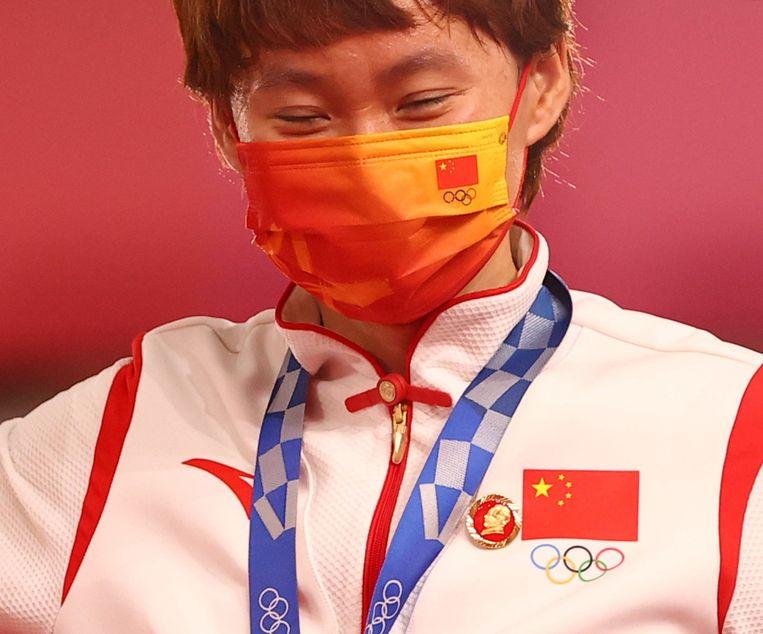Bao Shanyu met behalve haar gouden medaille, een button met de afbeelding van Mao.  Beeld REUTERS