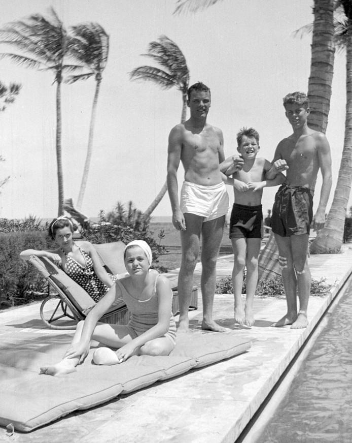 John F. Kennedy (rechts), Robert F. Kennedy (tweede van rechts) en Patricia Kennedy (vooraan links), samen met enkele vrienden aan het zwembad in Palm Beach, Florida.