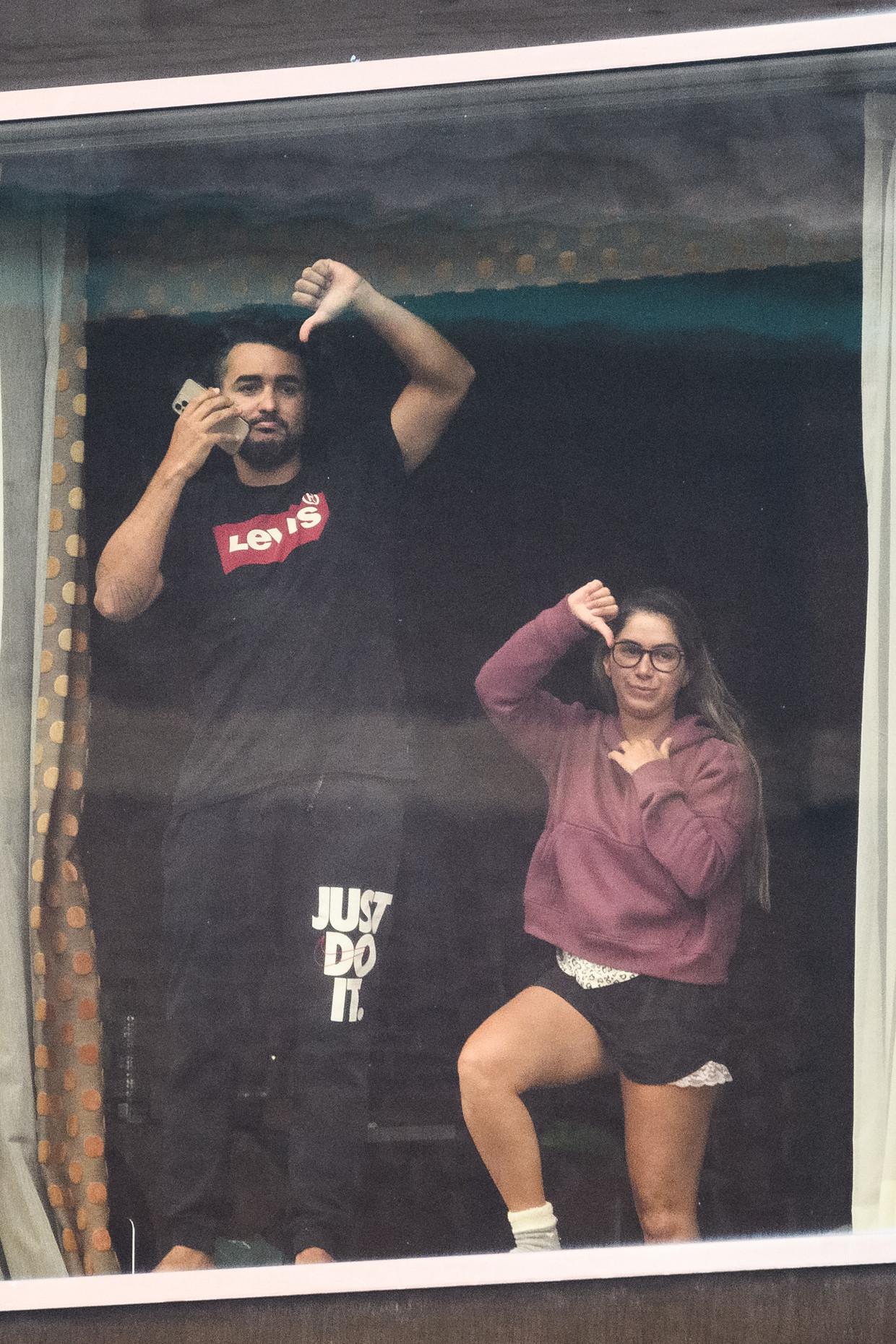 Vanuit een hotel aan de rand van Heatrow maken mensen hun onvrede met de quarantaine duidelijk.  Beeld Getty Images