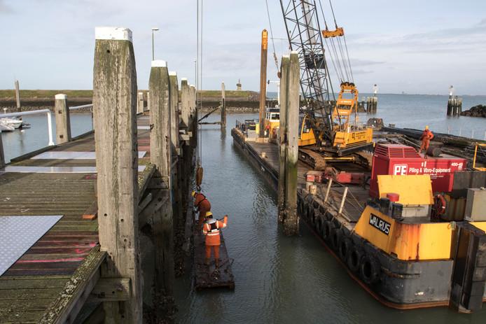 Vanaf werkschip de Walrus demonteren de mannen van aannemingsbedrijf Van der Straaten de versleten steiger in de haven van Colijnsplaat.