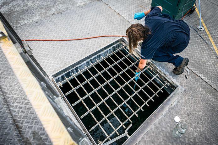 Een medewerker van de rioolwaterzuivering neemt een monster van het rioolwater. Dit wordt onderzocht op onder meer virusdeeltjes om zodoende te kunnen vaststellen hoeveel mensen het coronavirus onder de leden hebben en kunnen overdragen.