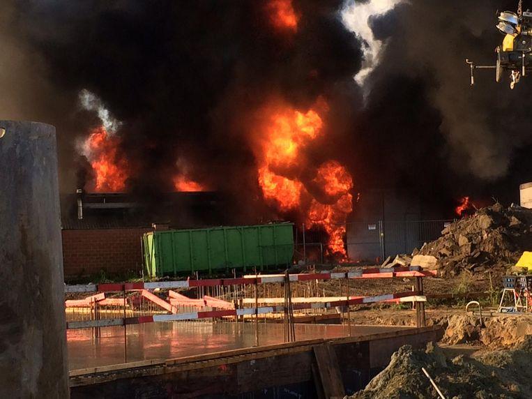 De brand woedt in alle hevigheid aan de achterkant van het gebouw.