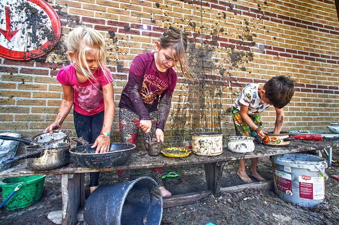 Kinderen maken onder leiding van juf Karin moddergerechten in de modderkeuken.