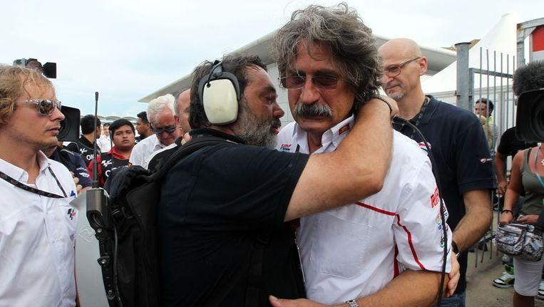 De vader van Marco Simoncelli wordt op Sepang getroost. Beeld afp