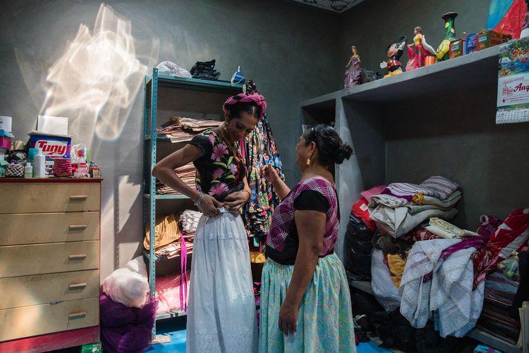 Estrella Vazquez, de eerste muxe-vrouw die eind 2019 op de cover van 'Vogue' verscheen, wordt bij het opkleden geholpen door haar moeder. Beeld ARIANA DREHSLER