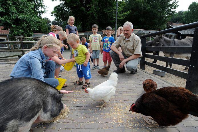 Beheerder Bertus Pols van de kinderboerderij in Zevenhuizen, hier in 2013, tussen de kinderen en dieren. Foto archief