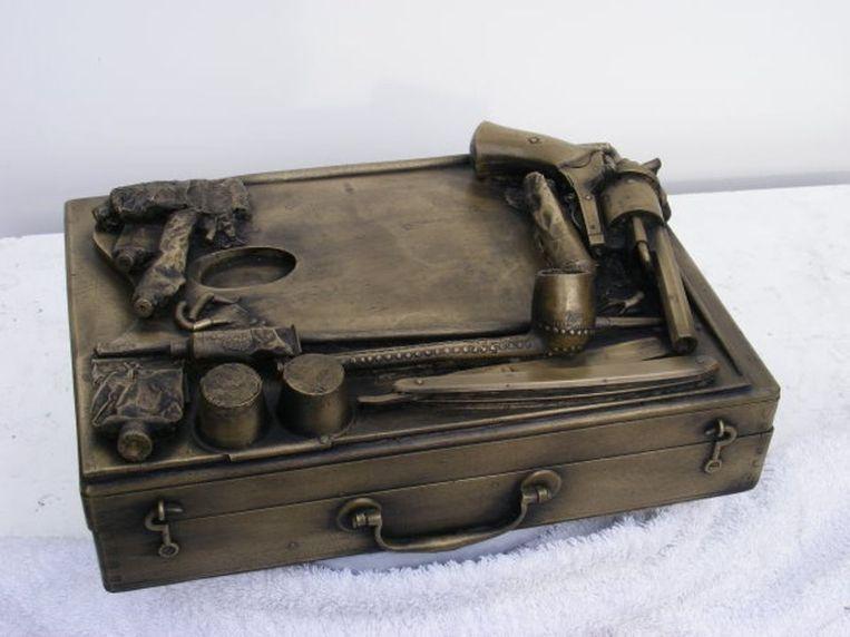 De originele maquette van de koffer met daarop een pijp, een scheermes en de revolver. Beeld
