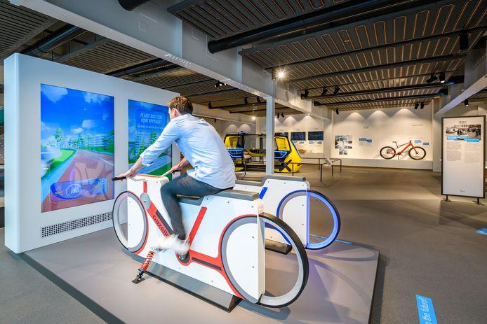 Een bezoeker probeert de fietssimulator