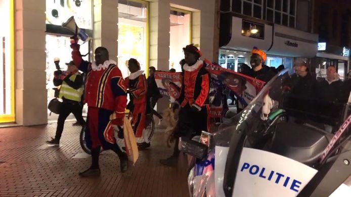 De pietendemonstranten lopen door de stad met een megafoon in Eindhoven