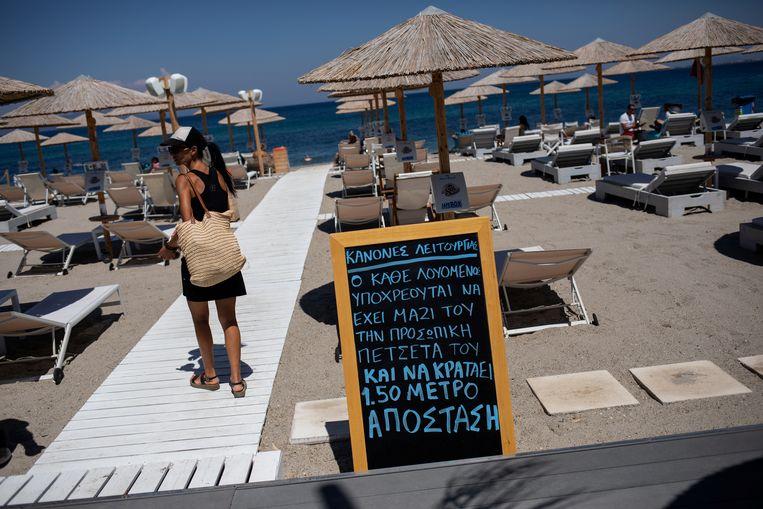 Een strand op het eiland Kos. Een bord maant aan om de social distancing te respecteren.