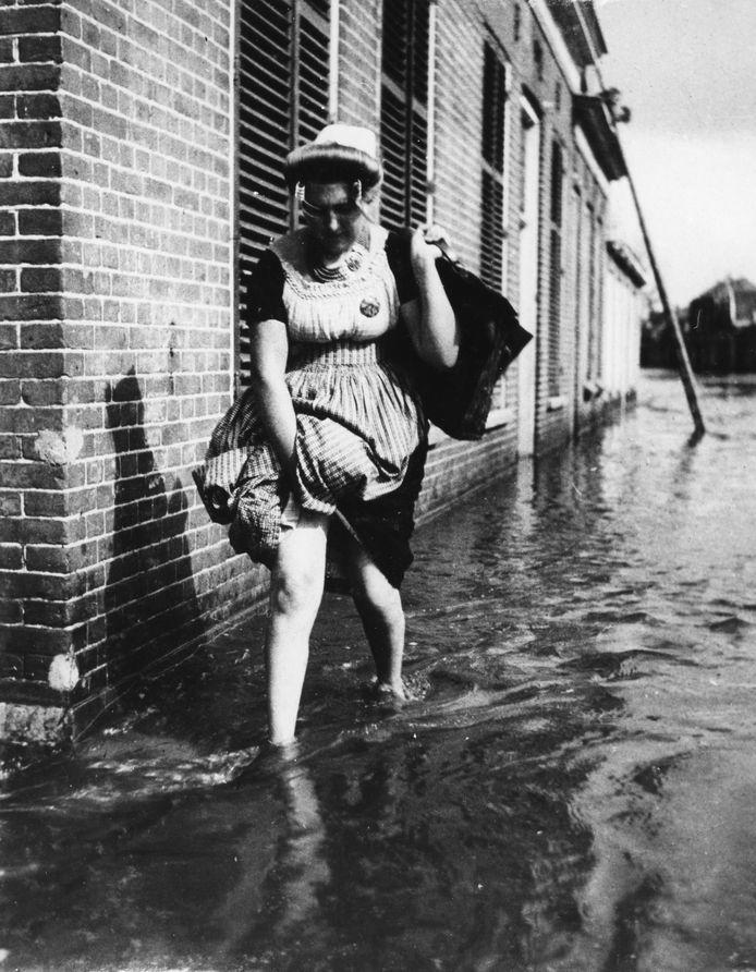 Serooskerke (Walcheren), 1945: Vrouw in Walcherse streekdracht loopt door het water van het geïnundeerde eiland, dat een jaar na de bevrijding nog steeds niet drooggemaakt is. foto Carel Blazer Maria Austria Instituut / ZB, Beeldbank Zeeland