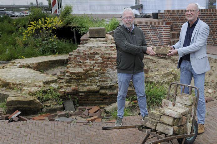Albert Corporaal (links) van het Hasselt's Mannenkoor overhandigt de eerste steen voor de reconstructie van de Veerpoort aan wethouder Harrie Rietman van Zwartewaterland.