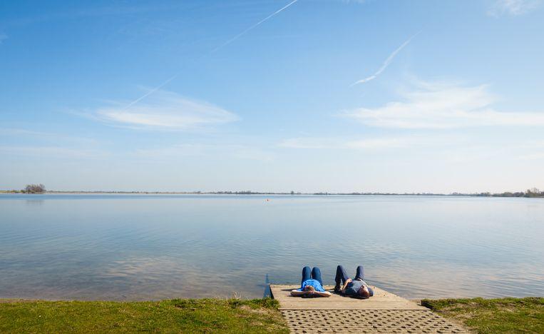 Twee mensen genieten van de zon aan de Reeuwijkse Plassen. Beeld Martijn Beekman