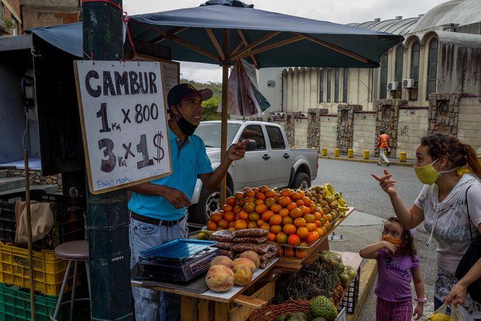 Ook deze straatverkoper in hoofdstad Caracas biedt zijn waren in dollarprijzen aan: drie kilo mandarijnen kost omgerekend een dollar of 0,84 euro.