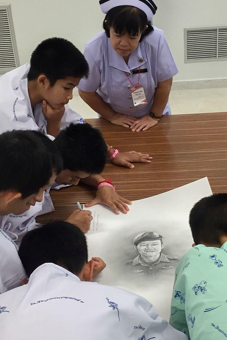De jongens schrijven kleine boodschapjes naast het portret van de overleden Saman Kunan.