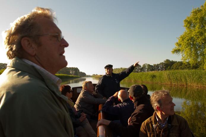 De schipper van de Berkelzomp wijst de toeristen op bijzondere vogels langs de Berkel bij Lochem.
