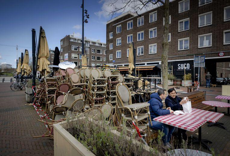 Twee mannen zitten aan een tafel van een gesloten terras op de Binnenrotte in Rotterdam.  Beeld ANP