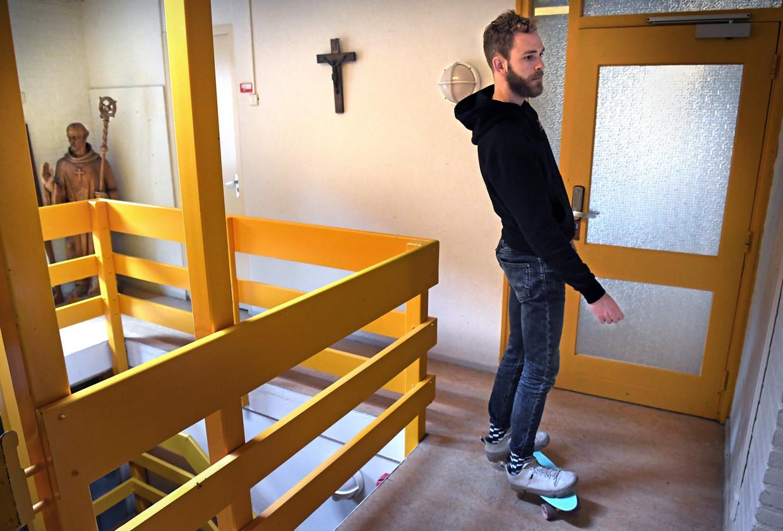 Een jongere gebruikt zijn skateboard om van zijn slaapkamer naar de leefruimte in het klooster in Deventer te gaan.  Beeld Marcel van den Bergh / de Volkskrant