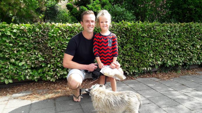 Nora met haar vader en de teddybeer die ze van de politie kreeg.