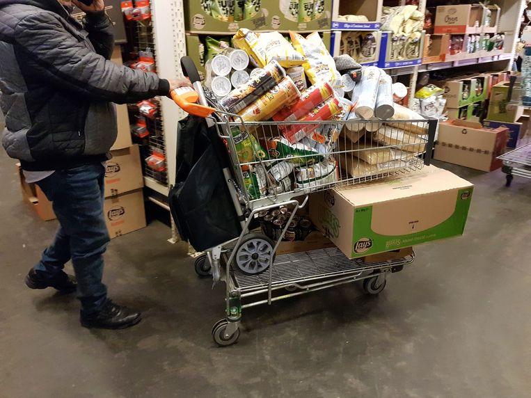Hamsteren in een Belgische supermarkt. In de grensregio steeg de verkoop van voeding en drank in de Belgische supermarkten. Beeld Photo News