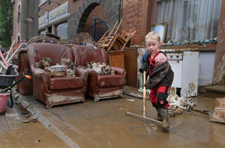 Een jongetje helpt met schoonmaken na de wateroverlast in Rochefort, België, 17 juli. Beeld AFP