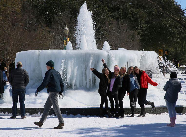 Studenten poseren voor een foto bij een bevroren fontein aan de universiteit van Baylor in Waco, Texas. Beeld AP