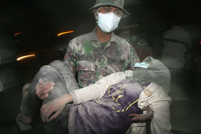 Een militair brengt een onwel geworden vrouw in veiligheid.
