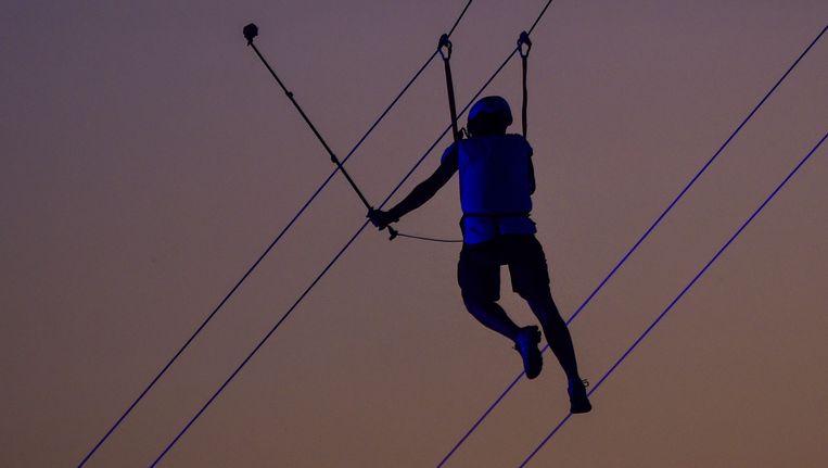 Een man met een selfiestick loopt over metalen kabels tijdens Rock in Rio. Beeld AFP