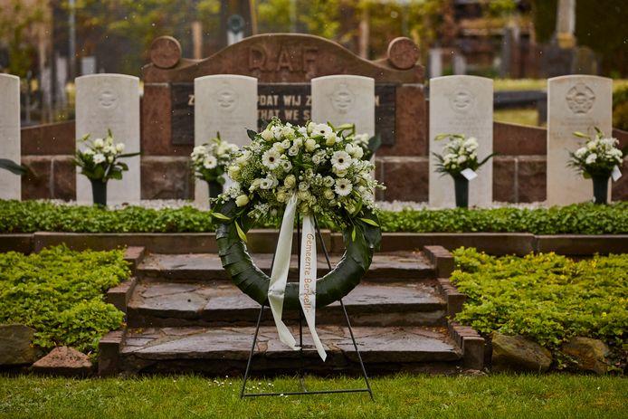 De krans van de gemeente Berkelland en bloemen bij de graven van de Britse en Canadese piloten op de Algemene Begraafplaats aan de Deugenweerd in Borculo.
