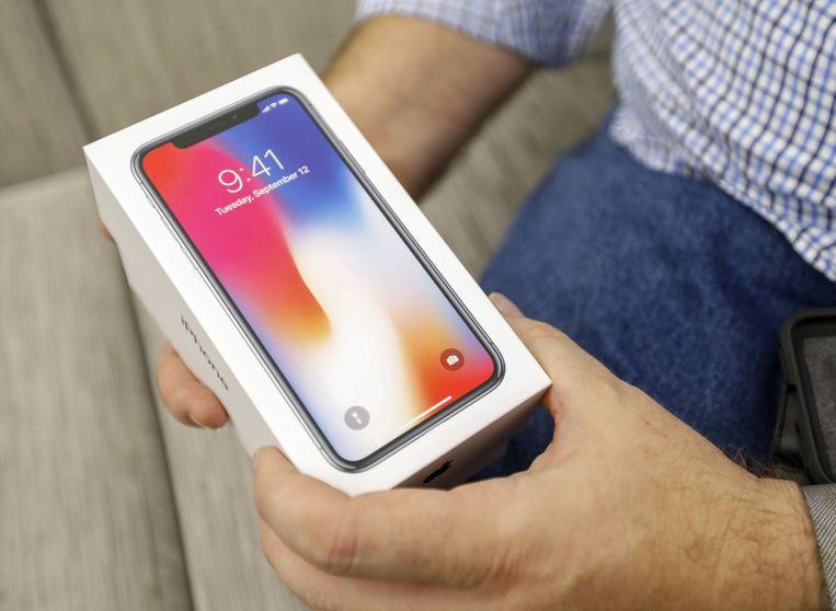 Een consument toont fier zijn iPhone X na aankoop in een winkelcentrum in de Amerikaanse stad Atlanta. De smartphone is bij ons te koop vanaf € 1.159. Beeld EPA